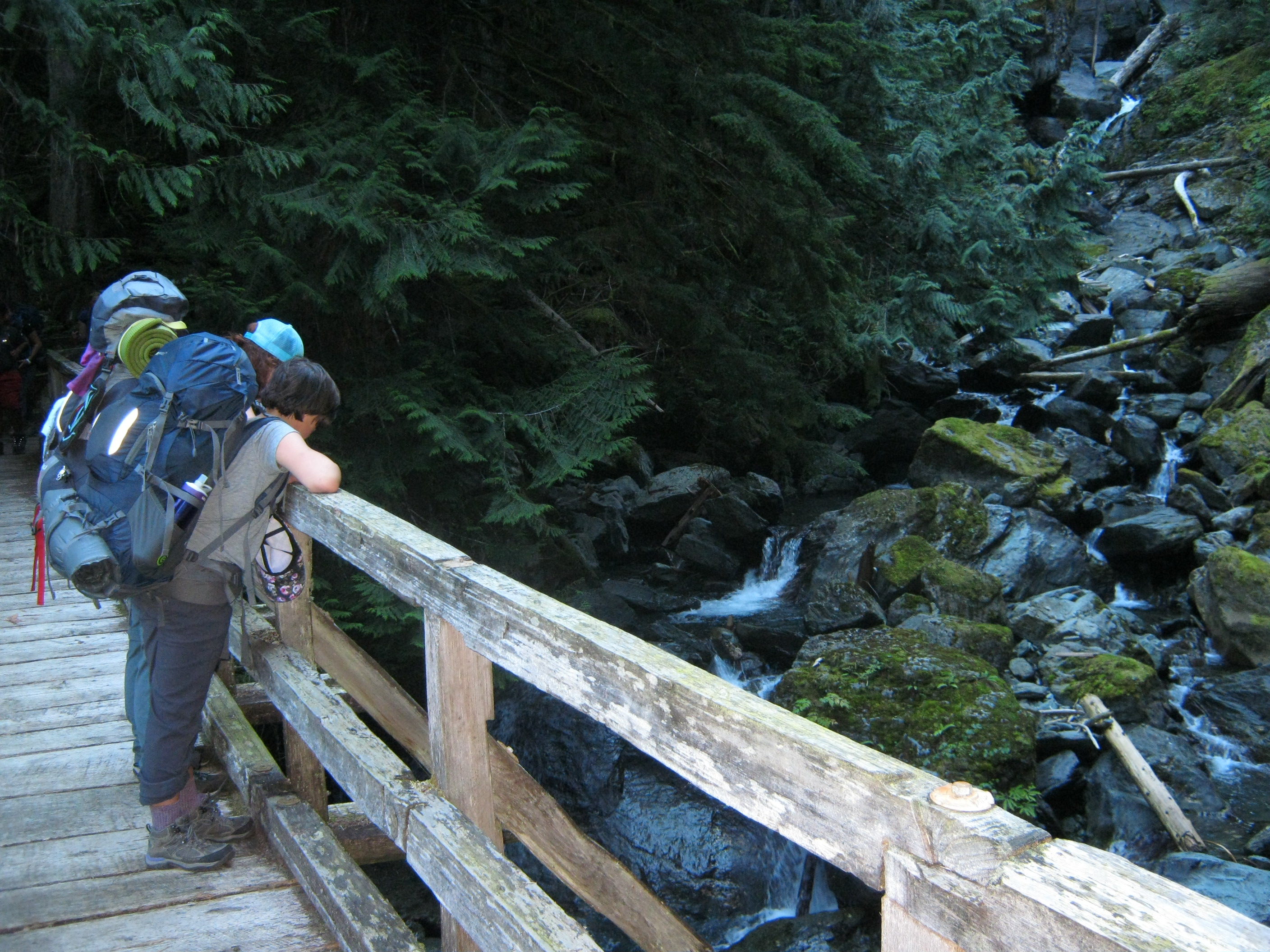 Two students with hiking backpacks on looking over the railing of a bridge at a stream below