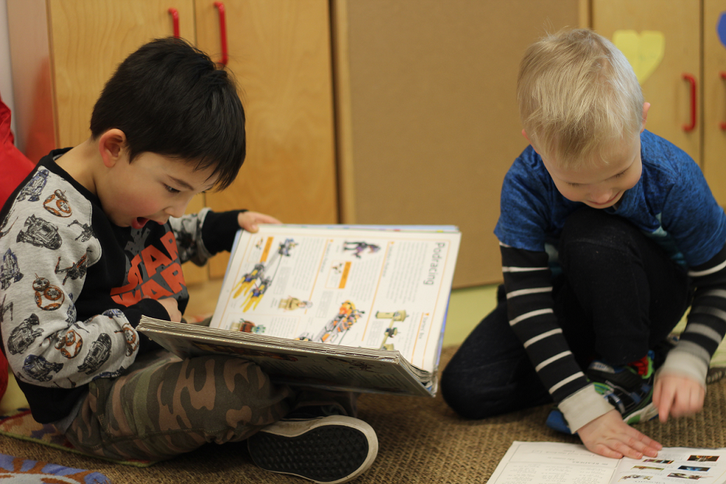Two preschool students sitting one the floor reading, one with their mouth ajar
