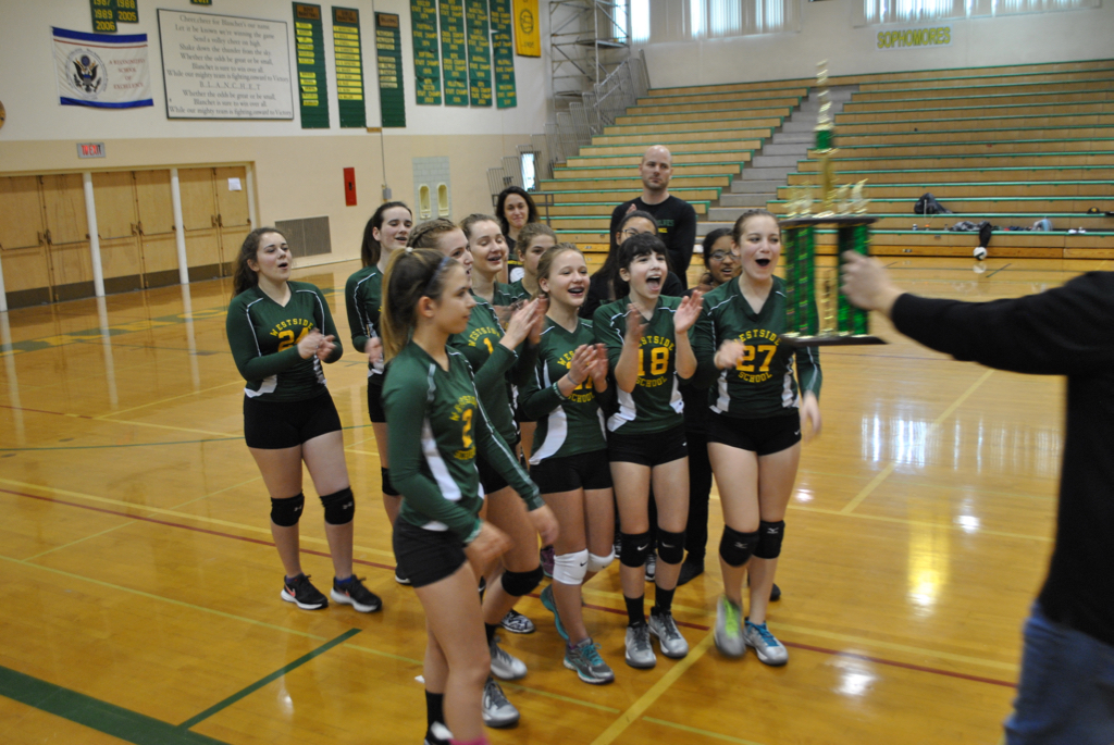 A middle school girls volleyball team cheering while being handed a trophy