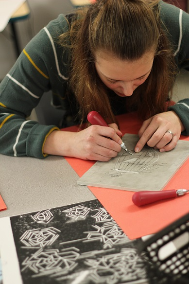 A middle school student creating a rubber stamp in art class
